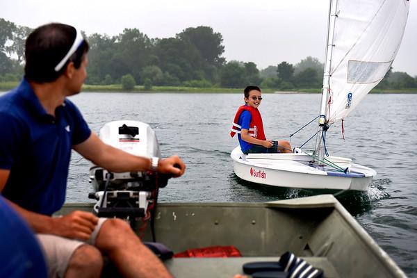 BEN MIKESELL | THE GOSHEN NEWS<br /> David Stutzman, 11, Goshen, gets help from instructor Bryan Bahler of Wawasee during Sail Camp Wednesay morning at Fidler Pond in Goshen.