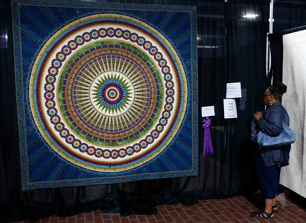 JOHN KLINE | THE GOSHEN NEWS<br /> Janice Allison of Chicago, Illinois, examines a quilt by Sherry Reynolds of Laramie, Wyoming, titled Eternal Beauty during the 2018 Shipshewana Quilt Festival Saturday. Reynolds earned the Best of Show title and $5,000 in prize money for the quilt, which took four years and 15,000 pieces to complete.