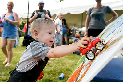 BEN MIKESELL | THE GOSHEN NEWS Jack Burgess of Holly, Michigan, 2, uses a toy truck to paint on a mural in the Young at Art tent during the Arts on the Millrace event Saturday in Goshen.