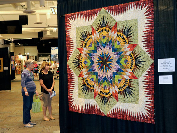 JOHN KLINE | THE GOSHEN NEWS<br /> Diana Strudwick, left, and Diane Ware, both of Sturgis, Michigan, examine one of the hundreds of quilts available for viewing during the 2018 Shipshewana Quilt Festival Saturday afternoon.
