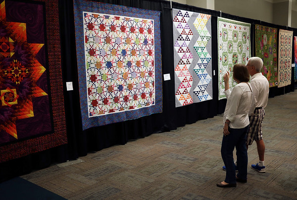 JOHN KLINE | THE GOSHEN NEWS<br /> From left, Pat and Marty Brennan of New Carlisle discuss one of the hundreds of quilts available for viewing during the 2018 Shipshewana Quilt Festival Saturday afternoon.