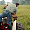 LIZ RIETH | THE GOSHEN NEWS <br /> Peter Cook, owner of Cook's Bison Ranch, shooes a bison away from his tractor Wednesday in Wolcottville.