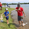 Roger Schneider| The Goshen News<br /> Sawyer Hummel, 6, of Goshen, catches a bluegill while his dad Lewie gives him a hand. The father and son were fishing in Saturday's Goshen Parks Department annual fishing tournament at Fidler Pond Park.