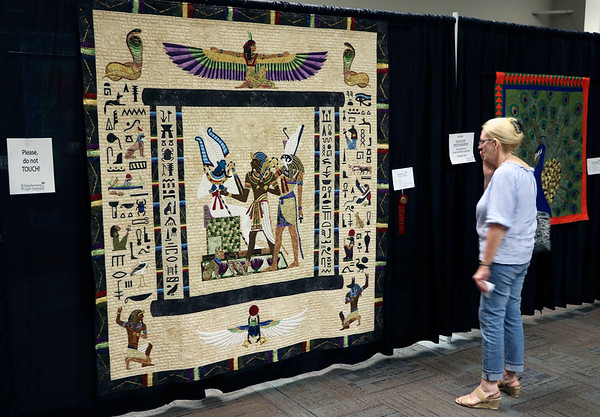 JOHN KLINE   THE GOSHEN NEWS<br /> Judy Kemp, of Chicago, Illinois, examines a quilt by Georgia Spalding Pierce of Seattle, Washington, titled Judgment of Osiris during the 2018 Shipshewana Quilt Festival Saturday. Pierce earned $500 in prize money for the quilt by taking second place in the Applique-Large category.
