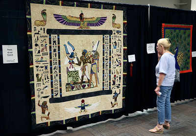 JOHN KLINE | THE GOSHEN NEWS Judy Kemp, of Chicago, Illinois, examines a quilt by Georgia Spalding Pierce of Seattle, Washington, titled Judgment of Osiris during the 2018 Shipshewana Quilt Festival Saturday. Pierce earned $500 in prize money for the quilt by taking second place in the Applique-Large category.