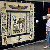 JOHN KLINE | THE GOSHEN NEWS<br /> Judy Kemp, of Chicago, Illinois, examines a quilt by Georgia Spalding Pierce of Seattle, Washington, titled Judgment of Osiris during the 2018 Shipshewana Quilt Festival Saturday. Pierce earned $500 in prize money for the quilt by taking second place in the Applique-Large category.
