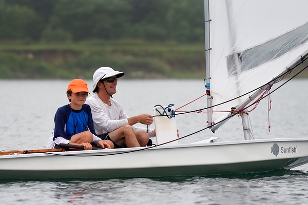 BEN MIKESELL | THE GOSHEN NEWS<br /> Jim Wellington, right, adjusts the sails while his son Pi, 12, watches during Sail Camp Wednesday morning at Fidler Pond in Goshen.