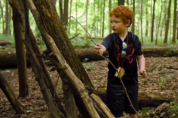 BEN MIKESELL | THE GOSHEN NEWS<br /> George Hedman, 7, Goshen, makes adjustments to his shelter made of tree branches during the Nature Explorer Day Camp Tuesday morning at Ox Bow Park.
