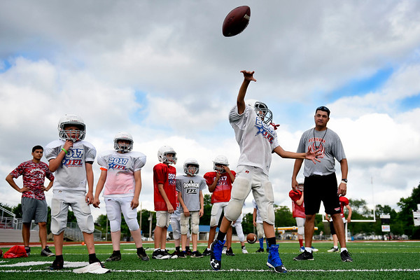 BEN MIKESELL | THE GOSHEN NEWS<br /> Goshen High School football head coach Kyle Park, right, observes throwing motions in a quarterback drill during the Goshen Junior Football League camp Tuesday at Foreman Field in Goshen. GHS varsity coaches and players attended the week-long camp as well to teach children drills and proper techniques.