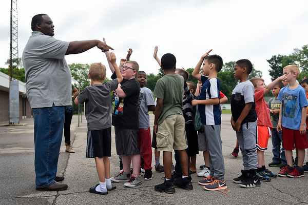 BEN MIKESELL   THE GOSHEN NEWS<br /> Clarence Thomas, employee with Thor Motor Coach, asks children at the Elkhart Boys and Girls Club how much an RV costs after they spent time touring three different sized RVs in the parking lot Wednesday morning.