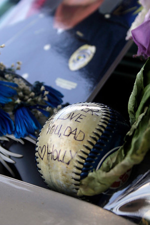 SHEILA SELMAN   THE GOSHEN NEWS<br /> A baseball written on by Chief Wade Branson's daughter rests against his police vehicle Saturday afternoon.