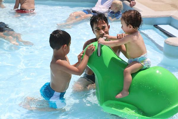 SHEILA SELMAN | THE GOSHEN NEWS<br /> Juan Cedeno, Goshen, helps his nephew, Antony Cedeno ride the frog in the kiddie pool at Shanklin Pool Sunday afternoon.