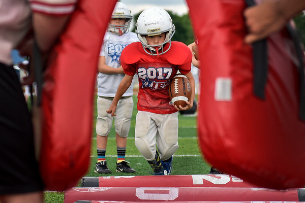 BEN MIKESELL | THE GOSHEN NEWS<br /> Kaden Robinson, 9, Goshen, gets ready to hurdle over pads in a running back drill during the Goshen Junior Football League camp Tuesday at Goshen High School.