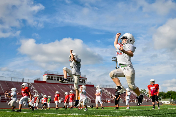 BEN MIKESELL | THE GOSHEN NEWS<br /> Goshen Junior Football League campers warm up with calisthenics drills Tuesday at Goshen High School. GHS has hosted the JFL camp every summer for the past six years.