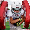 BEN MIKESELL | THE GOSHEN NEWS<br /> Jaden Keim, 10, of Goshen pushes through the pads in a running back drill Tuesday evening during the Goshen Junior Football League camp this week at Goshen High School's Foreman Field.