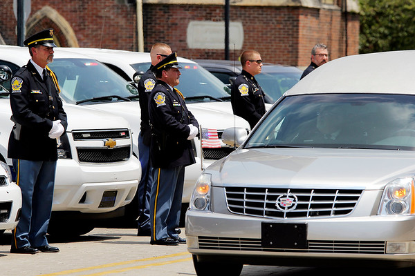 SHEILA SELMAN | THE GOSHEN NEWS<br /> Goshen police officers stand in front of their squard cars in honor of Police Chief Wade Branson as the hearse passes the Goshen Police Department Saturday afternoon.