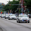 AIMEE AMBROSE | THE GOSHEN NEWS<br /> <br /> Police vehicles drove in a procession on Main Street through downtown Goshen Saturday on their way to West Goshen Cemetery following the funeral of Goshen Police Chief Wade Branson, who died from cancer on Monday.