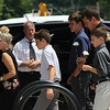 SHEILA SELMAN | THE GOSHEN NEWS<br /> Goshen Police Chief Wade Branson's family, led by wife Sue, stopped the processional to lay flowers on his police vehicle Saturday afternoon.