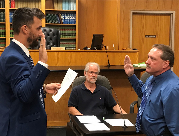 JOHN KLINE   THE GOSHEN NEWS<br /> Goshen Mayor Jeremy Stutsman, left, swears in Keith Miller, right, following his promotion from the rank of patrol captain to the rank of division chief of investigations with the Goshen Police Department during Monday's Board of Public Works and Safety meeting.