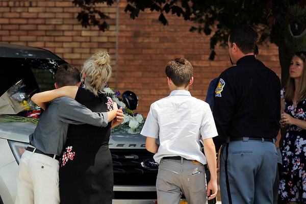 SHEILA SELMAN | THE GOSHEN NEWS<br /> Goshen Police Chief Wade Branson's family stopped the processional for a moment to lay flowers on his police vehicle parked in front of the Goshen Police Department Saturday afternoon.