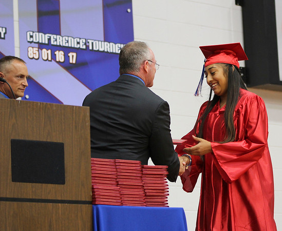 SHEILA SELMAN | THE GOSHEN NEWS<br /> West Noble High School Principal Greg Baker hands Esra Andrade her diploma during West Noble's commencement Sunday afternoon.