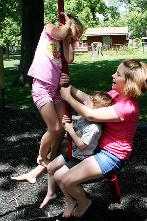 SHEILA SELMAN | THE GOSHEN NEWS<br /> Hazel Looney, 8, Goshen, left, stands overJosiah Looney, 4, Goshen, and Cailin Clark, 10, Syracuse, on a piece of playground equipment at Sunnyside Park in New Paris Monday afternoon.