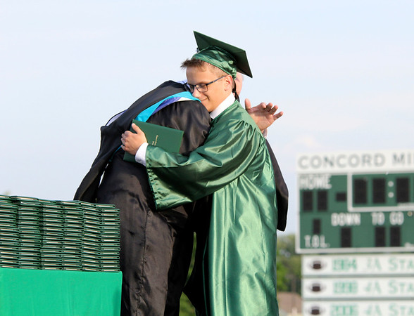 SHEILA SELMAN | THE GOSHEN NEWS<br /> Joshua Riker, right, hugs Concord High School Principal Greg Dettinger as he accepts an honorary diploma for his twin sister, Mary, who died during the school year.
