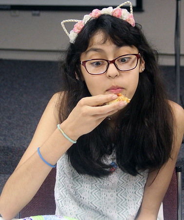 Camila Sandoval, 13, takes another piece of pizza at GPL Teen PizzaFest June 7.
