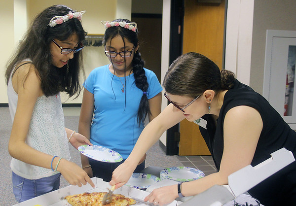 Liz Rieth | The Goshen News<br /> From left, Camila Sandoval, 13, Melissa Ortega, 12, and Emily Stuckey Weber, GPL teen services coordinater, choose their next pieces of pizza at GPL Teen PizzaFest Thursday.