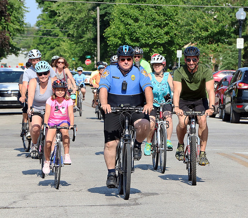 Roger Schneider | The Goshen News<br /> Goshen police officer Thomas Fuller, center, and Mayor Jeremy Stutsman, right, lead riders down East Washington Steet Thursday night on the third annual Mayor's Bike Ride. The ride is held to promote Bike to Work Week, which is being observed this week. The riders intended to ride down the millrace path to the Elkhart River dam and then continue through town and end the ride with ice cream at The Chief.