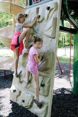 SHEILA SELMAN | THE GOSHEN NEWS<br /> Caroline Looney, 10, Goshen, left, and Hazel Looney, 8, Goshen, climb the wall at Sunnyside Park in New Paris Monday afternoon.