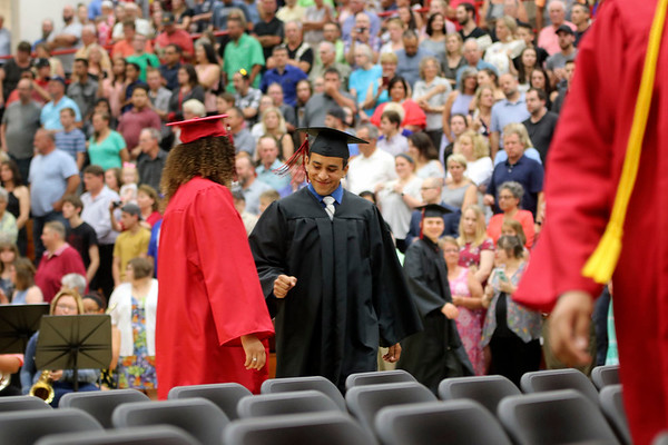 Geoff Lesar | The Goshen News<br /> NorthWood High School graduate Juan Pantoja, of Nappanee, bumps fists with a fellow graduate during the school's commencement ceremony Friday evening in Nappanee.