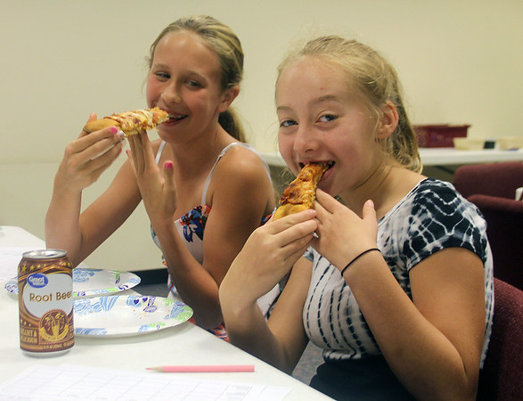 Liz Rieth | The Goshen News<br />  Haily Hall, 12, left, and Kiersten Yoder, 11, eat pizza at GPL Teen PizzaFest Thursday.