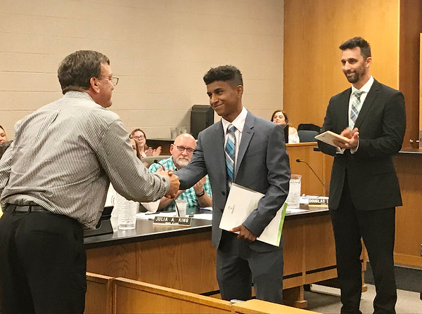 JOHN KLINE | THE GOSHEN NEWS<br /> Vince Turner of MutualBank, left, shakes hands with Jason Barahona, 2017-18 youth adviser to the Goshen City Council, center, during Barahona's send-off at the Goshen City Council meeting Tuesday evening. Also pictured is Goshen Mayor Jeremy Stutsman, right, who together with Turner and MutualBank provided Barahona with a $1,000 scholarship in recognition of his service to the city.