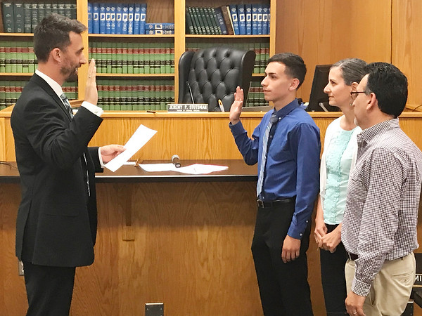 JOHN KLINE | THE GOSHEN NEWS<br /> Goshen Mayor Jeremy Stutsman, left, swears in Goshen High School student Felix Perez-Diener, second from left, as the Goshen City Council's new youth adviser for the 2018-19 school year during Tuesday's council meeting. Also pictured are Perez-Diener's parents, from left, Denise Diener and Gilberto Perez Jr.