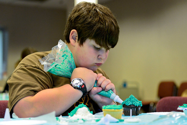 "BEN MIKESELL | THE GOSHEN NEWS Phillip Yoder, 11, of Goshen concentrates on his cupcake creation during Maker Monday's Cupcake Wars at Goshen Public Library. During the competition, Yoder and seven other children worked to create the best ""book-to-cupcake"" design to be chosen by the judges, librarian Tina Ervin and teen services coordinator Emily Stuckey Weber."