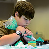 "BEN MIKESELL | THE GOSHEN NEWS<br /> Phillip Yoder, 11, of Goshen concentrates on his cupcake creation during Maker Monday's Cupcake Wars at Goshen Public Library. During the competition, Yoder and seven other children worked to create the best ""book-to-cupcake"" design to be chosen by the judges, librarian Tina Ervin and teen services coordinator Emily Stuckey Weber."