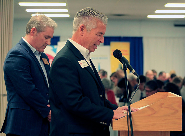 Roger Schneider | The Goshen News<br /> Jim Caskey, left, chairman of the Goshen Chamber of Commerce board of directors, and Bob Schrock, CEO of DJ Construction, bow their heads as Schrock gives the invocation before the start of the Goshen Founder's Day event Thursday.