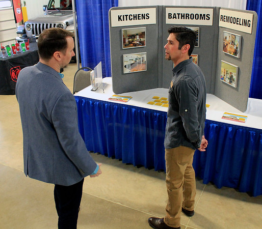 Roger Schneider | The Goshen News<br /> Todd Ruth of Digital Hill, left, chats with Gary Klingerman of Bail Home Construction at the Goshen Foudner's Day trade show Thursday.