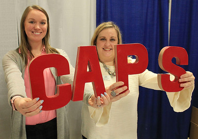 Roger Schneider | The Goshen News Claire Powell, left, fundraising manager, and Leah Plan, parent aid director, hold up some letters that spell out their agency's name during the trade show portion of the Goshen Founder's Day event Thursday.