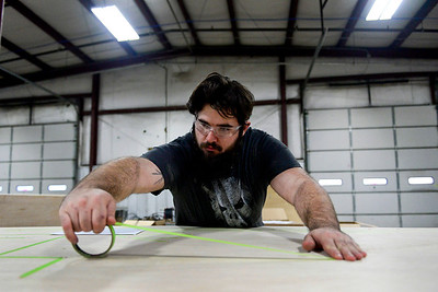 BEN MIKESELL | THE GOSHEN NEWS Daniel Harris, worker at Thor Motor Coach, maps out lines on board for running cables Tuesday at Thor's factory in Wakarusa.