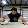 BEN MIKESELL | THE GOSHEN NEWS<br /> Daniel Harris, worker at Thor Motor Coach, maps out lines on board for running cables Tuesday at Thor's factory in Wakarusa.