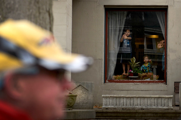 BEN MIKESELL | THE GOSHEN NEWS<br /> A family watches and waves from their home on Fifth Street as protesters with March for Our Lives walk down the sidewalk Saturday toward the Elkhart County Courthouse.