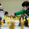 BEN MIKESELL | THE GOSHEN NEWS<br /> Parkside Elementary School fourth-grader Roman Nyce reaches across the table to move his queen while playing against Waterford Elementary fourth-grader Ivan Sanchez Hernandez Tuesday during the Goshen City Wide Tournament at Chandler Elementary. Students from five Goshen elementary schools were invited to Chandler to compete for the trophy, which has been passed from school to school since the tournament's inception in 1993.