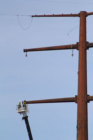 ROGER SCHNEIDER | THE GOSHEN NEWS<br /> Two workersr with PAR Electrical Contractors Inc. of Kansas City, Missouri, work in a bucket at the top of a crane to install equipment on a new electric transmission tower at C.R. 29 and U.S. 6 Monday. The tower is one of many that make up the new100-mile  NIPSCO transmission line from Reynolds and Burr Oak to Topeka. The project is expected to be completed late this year, according to NIPSCO's website.