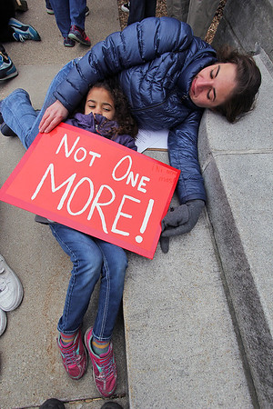 ROGER SCHNEIDER | THE GOSHEN NEWS<br /> <br /> Kristina Behan Morillo, 7, lays with her mother Erin on the steps of the Elkhart County Courthouse as the names of the 17 people killed at Marjory Stoneman Douglas High School in Parkland, Florida are read during the March for our Lives event. Erin Morillo is a teacher in Elkhart and spoke to the crowd.