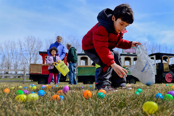 BEN MIKESELL | THE GOSHEN NEWS<br /> Nathaniel Mayer, 7, of Granger scoops up Easter eggs Friday at Linton's Enchanted Gardens in Elkhart during its Easter Egg-Straordinaire. Goats, lambs and other farm animals were available to pet and feed in the greenhouse, and children could ride a train through the gardens to hunt for eggs.