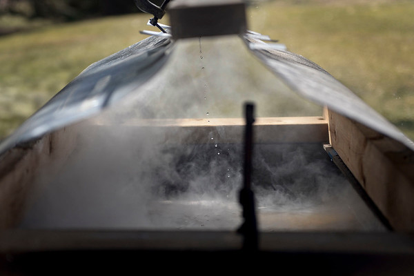 BEN MIKESELL | THE GOSHEN NEWS<br /> Sap drips into a vat of syrup in the backyard of Glenn Stutzman's home in Goshen. Stutzman hand-crafted the hood that rests over the tray in order to keep ash from getting into the batch.