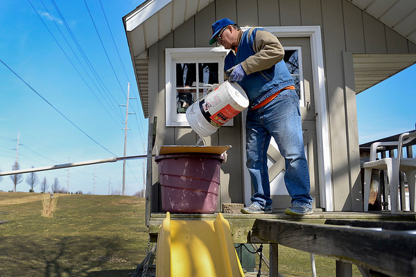 BEN MIKESELL | THE GOSHEN NEWS<br /> Glenn Stutzman dumps tree sap into a bucket on the playground in his backyard, which is rigged to drip into the vat below as he makes a batch of maple syrup Monday at his house in Goshen.