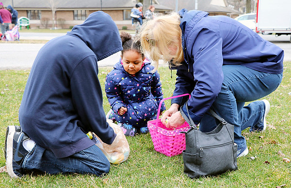 JOHN KLINE | THE GOSHEN NEWS<br /> Brielle Phillips, 3, of Elkhart, center, gets some help opening her candy-filled Easter eggs from uncle Malik Woods, 12, of Middlebury, left, and great-grandmother Cinda Olinger, of Middlebury, right, following Saturday's annual Middlebury Township Fire Department Easter Egg Hunt at Memorial Park in downtown Middlebury.